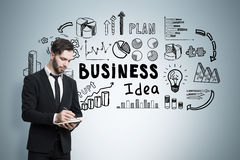 Man with paper, business idea,. Bearded businessman with a notebook is writing while standing near a gray wall with business idea icons Royalty Free Stock Images