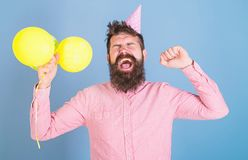 Man in paper cap isolated on blue background. Daddy exhausted after day with kids, International children day. Celebration. Hipster with trendy beard yawning stock images