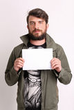 Man with paper. Close up. White. Man with paper, man with white sheet, man wearing khaki jacket, serious man, beard and mustache, casual clothes, unshaven, in Royalty Free Stock Photography
