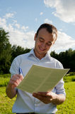 Man with paper and pen in the park Royalty Free Stock Image