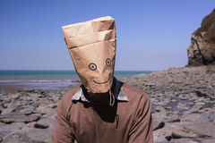 Man with paperbag over his head on the beach Royalty Free Stock Images