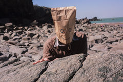 Man with paperbag over his head on the beach Royalty Free Stock Photo