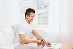 Man with papers and calculator at home Stock Images