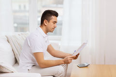 Man with papers and calculator at home Royalty Free Stock Photos