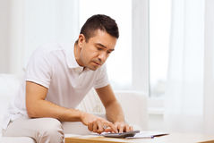 Man with papers and calculator at home Royalty Free Stock Photo