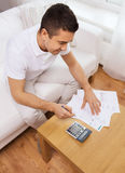 Man with papers and calculator at home. Business, savings, finances and people concept - man with papers and calculator at home counting and filling tax form Royalty Free Stock Photography