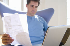 Man with paperwork in armchair, low angle view Royalty Free Stock Photos