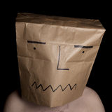 Man with papper bag in head. Self portrait of a man with a brown papper bag covering his head. Image shot in a studio environment and on a black background Royalty Free Stock Images