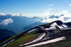 A man on a parachute flies over the mountains high above the world stock photo