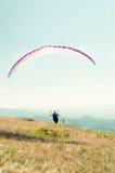 Man paraglider preparing to take off Stock Photo