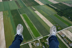 Man paragliding above  fields Royalty Free Stock Photography
