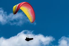 Man paragliding through the afternoon sky. Man Paragliding in the sky on a blue sky sunny afternoon Stock Photography