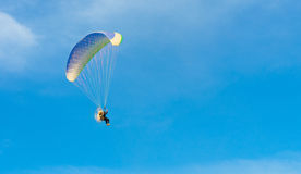 Paraglider on blue bright sky. A man and paramotor on blue sky Stock Photography