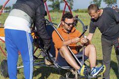 Man with paraplane. JUNE 20, 2017: Assistant helps the paraglider to straighten the paraplane before the flight in Bulgaria Royalty Free Stock Images