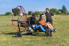 Man with paraplane. JUNE 20, 2017: Assistant helps the paraglider to straighten the paraplane before the flight in Bulgaria Royalty Free Stock Photography