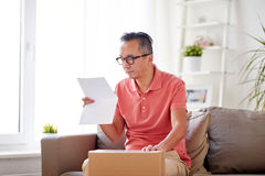 Man with parcel box reading invoice at home Royalty Free Stock Images