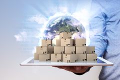 Man Hand Tablet PC Globalization. Man with parcels on the tablet pc and globe on the backdrop Royalty Free Stock Images