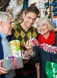 Man With Parents Shopping In Christmas Store Stock Images