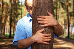 Man in park. Man hiding behind a tree Royalty Free Stock Image