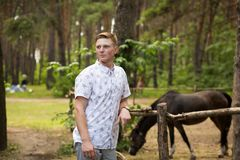 A man in a park with a horse. A man in a park with a black horse Royalty Free Stock Photography