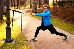 A man in a park improving his legs flexibility. A man in a park improving his legs flexibility with fitness trx strips Royalty Free Stock Image