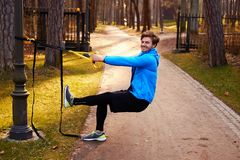 A man in a park improving his legs flexibility. A man in a park improving his legs flexibility with fitness trx strips Stock Photos