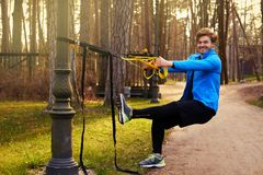 A man in a park improving his legs flexibility. A man in a park improving his legs flexibility with fitness trx strips Royalty Free Stock Photo