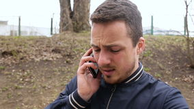 Man in park with mobile phone stock video footage