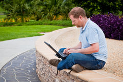 Man in park using laptop computer Royalty Free Stock Images