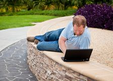 Man in park using laptop computer Royalty Free Stock Photo