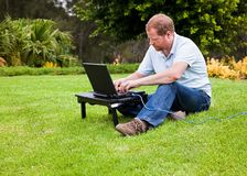 Man in park using laptop with ethernet cable Royalty Free Stock Photos