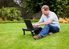 Man in park using wireless laptop computer Royalty Free Stock Image