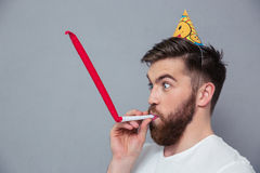 Man with party hat blowing in whistle Stock Image