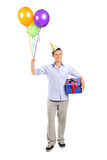 Man with party hat holding balloons Royalty Free Stock Image