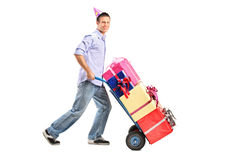 Man with a party hat pushing a hand truck Stock Image