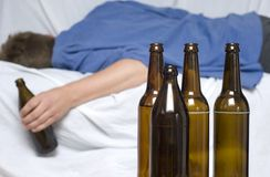 Man passed out with a beer bottle in his hand. Alcohol abuse Stock Photography