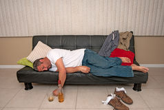 Man passed out drunk. Depressed man drunk and passed out on couch Royalty Free Stock Image