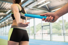 Man passing the baton to partner on track. At the gym royalty free stock photos