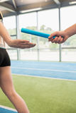 Man passing the baton to partner on track. At the gym royalty free stock image