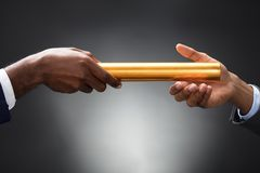 Man Passing The Golden Baton To His Partner. On Gray Background stock photography