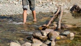 Man passing through the mountain river. Man passing through the shallow part of the mountain river stock footage
