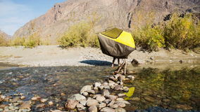 Man passing through the mountain river. With a tent in his hands stock video