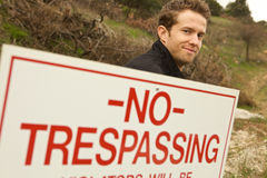 A Man Passing No Trespassing Sign Stock Photo