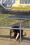 Man passing under the wires in a mud ground Stock Photo