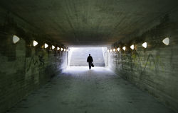 Man passing through underpass. Shadowy man passing through atmospheric underpass Stock Photos