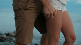 Man passionate hand squeezes women in short shorts on a rocky beach. On the sea coast a young couple stands and hugs stock footage