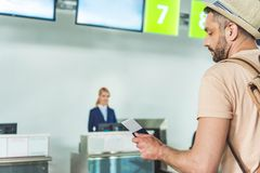 Man with passport and ticket. Side view of men holding passport and ticket in hand while waiting at check in desk at airport Royalty Free Stock Images