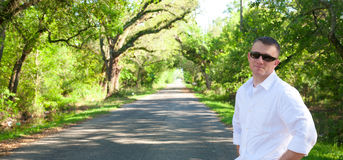 Man on Path to Success. A man with a road lined with oak trees and blue sky in the background Stock Image