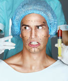 Man patient with horror looks at scalpel. Royalty Free Stock Images