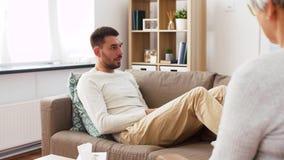 Man patient talking to senior woman psychologist stock video footage